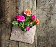 Rosa floresce no envelope do papel do ofício sobre o fundo de madeira Fotografia de Stock