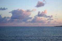 Rosa fluffiga moln över havet arkivbild