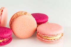 Rosa francés y macarons o macarrones magentas, primer, opinión superior del lado sobre un fondo blanco imagenes de archivo