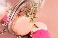 Rosa französische macarons oder Makronen, fallend aus einem Glasgefäß mit kleinen gelben Blumen über einem rosa Hintergrund herau lizenzfreie stockbilder