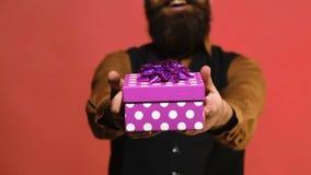 Rosa gåvaask i händerna av en man på en röd bakgrund Mannen framlägger en gåva för ferier Begrepp för dag för valentin` s arkivfilmer