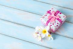 Rosa gåvaask med blommor på trägolv Fotografering för Bildbyråer