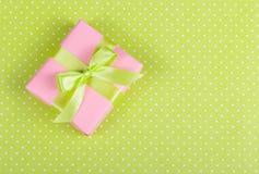 Rosa gåvaask med en pilbåge på ett ljus - grön bakgrund Ask med överraskning på en prickbakgrund Arkivbild