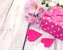 Rosa gåvaask med hjärta och blommor på lantlig vit trätabl Royaltyfri Foto