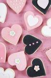 Rosa, galletas hechas en casa blancos y negros de la forma del corazón en fondo de madera rosado elegante lamentable del vintage Imagenes de archivo