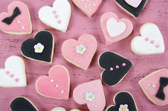 Rosa, galletas hechas en casa blancos y negros de la forma del corazón en fondo de madera rosado elegante lamentable del vintage Imágenes de archivo libres de regalías