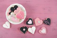 Rosa, galletas hechas en casa blancos y negros de la forma del corazón en fondo de madera rosado elegante lamentable del vintage Foto de archivo libre de regalías