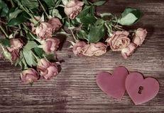 Rosa Gartenrosen und -herzen des Malls auf Holzoberfläche Retrostilromantischer Blumenhintergrund Rosa Herz zwei Stockbild