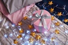 Rosa Geschenk auf dem Tisch mit Sternlichtern Stockbild
