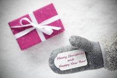 Rosa Geschenk, Handschuh, frohe Weihnachten, guten Rutsch ins Neue Jahr, Schneeflocken Stockfotos