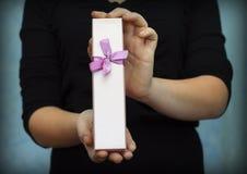 Rosa Geschenkbox in den Händen Stockbild
