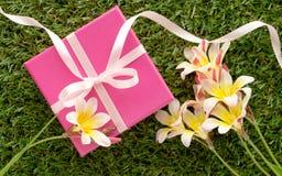 Rosa Geschenkbox mit einem Bogen und Blumen Stockfotos