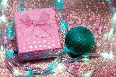 Rosa Geschenkbox mit einem dunkelgrünen Weihnachtsball auf einem purpurroten funkelnden Hintergrund lizenzfreie stockfotos