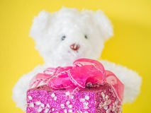 Rosa Geschenkbox und undeutlicher weißer Bär spielen mit gelber Wand Stockfotografie