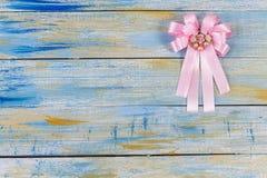Rosa Gewebebogen auf farbigem hölzernem Hintergrund Lizenzfreies Stockbild