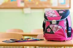Rosa girly Schultasche- und Bleistiftkasten auf einem Schreibtisch in einem leeren Klassenzimmer Lizenzfreie Stockfotos