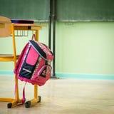 Rosa girly Schultasche- und Bleistiftkasten auf einem Schreibtisch in einem leeren Klassenzimmer Erster Tag der Schule Lizenzfreies Stockbild