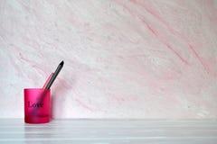 Rosa Glas mit Bleistiften und Stift Stockbild