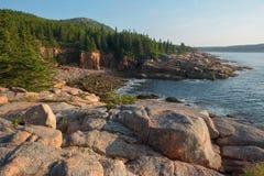 Rosa Granitfelsen und -klippen, die eine ziemlich abgelegene Bucht übersehen Stockfotos