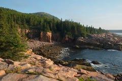 Rosa Granitplatten und -flusssteine auf einem abgelegenen Bereich des Strandes in M Lizenzfreie Stockbilder