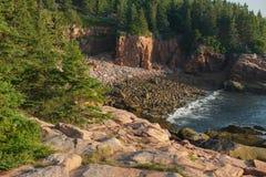 Rosa Granitplatten und -flusssteine auf einem abgelegenen Bereich des Strandes in M Stockfotos