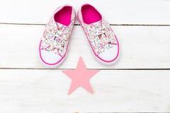Rosa gymnastikskor för barn` s och en rosa stjärna på en träbakgrund arkivbild