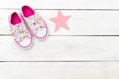 Rosa gymnastikskor för barn` s och en rosa stjärna på en träbakgrund royaltyfri fotografi