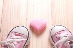 Rosa gymnastikskor för flicka` s med rosa hjärtor på ett trägolv, Arkivbilder