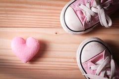 Rosa gymnastikskor för flicka` s med rosa hjärtor på ett trägolv Arkivfoto