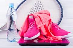 Rosa gymnastikskor och en T-tröja, för kondition, på elektronisk våg, en flaska av vatten, på en grå bakgrund och tennisracket Arkivfoto