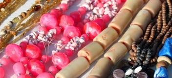 Rosa halsband med andra smycken som är till salu i tappningen, shoppar arkivbilder