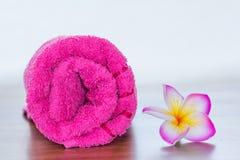 Rosa handduk med frangipaniblomman Fotografering för Bildbyråer