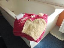 Rosa handduk på badkaret med badhandsken Royaltyfria Bilder
