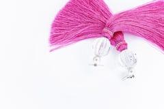 Rosa handgemachte Ohrringe auf einem weißen Hintergrund Stockfotos