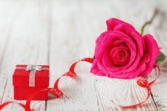Rosa hermosa del rosa con la caja de regalo, día de fiesta presente en el fondo de madera blanco Fotografía de archivo