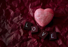 Rosa Herz auf rotem Hintergrund mit Liebesfliesen Lizenzfreie Stockfotos