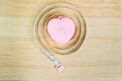 Rosa Herz messendes Band auf Holz Stockbilder