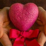 Rosa Herz mit rosa Bogen in Frau ` s Händen Lizenzfreie Stockbilder
