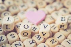 Rosa Herz mit Wort-Liebe in Alphabet-Hintergrund-Weinlese-Ton, V Stockfotos