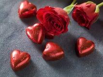 Rosa Herz zwei Rote Rosen und Schokoladenherzen auf gre Lizenzfreie Stockbilder