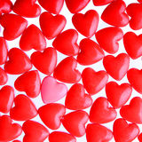 Rosa Herz zwischen einem Stapel von roten Herzen. Süßigkeits-Herzhintergrund Stockbilder