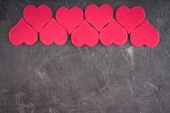 rosa Herzen auf einem grauen Hintergrund Das Symbol des Tages der Liebhaber Zwei verklemmte Innere Konzept am 14. Februar Stockfotografie