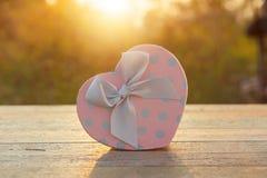 Rosa Herzgeschenkbox auf hölzerner Tabelle im Sonnenuntergang Stockbilder