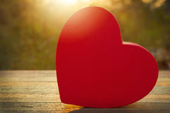 Rosa Herzgeschenkbox auf hölzerner Tabelle im Sonnenuntergang Lizenzfreies Stockfoto