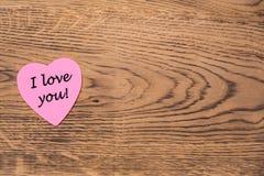 Rosa Herzhaftnotiz mit dem Text 'ich liebe dich 'auf einem hölzernen Hintergrund stockbilder
