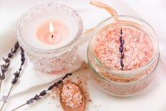 Rosa Himalajasalz im Glasgefäß, hölzerner Löffel der brennenden Kerze, Lavendel auf weißem Baumwollstoff, redete Foto für Social  Stockfotografie