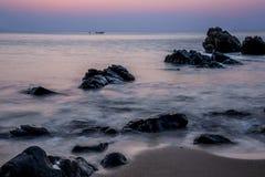 Rosa Himmel über einer felsigen Küste. Sonnenunterganglandschaft. Thailändisches Boot. Tropeninsel. stockfoto