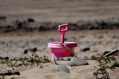 Rosa hink och spade på stranden Fotografering för Bildbyråer