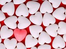 Rosa hjärta mellan en hög av vita hjärtor. Godishjärtor Royaltyfria Bilder