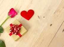 Rosa hjärta- och gåvaask på ett trägolv Royaltyfri Foto